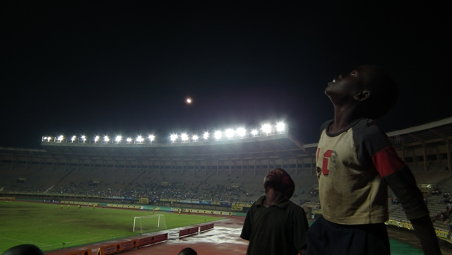 Young boys watching a helicopter traversing the Namboole skies